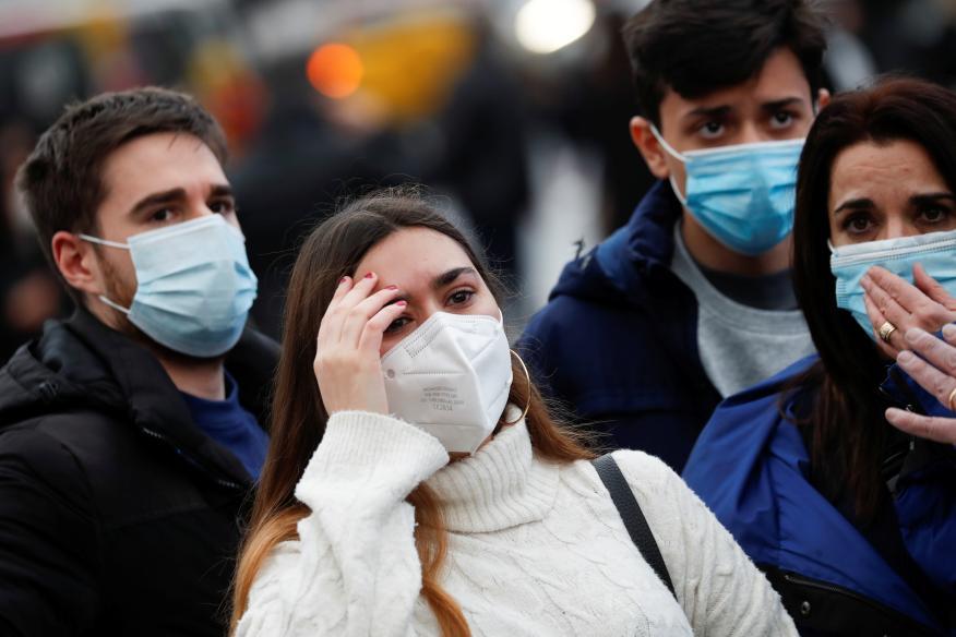Jóvenes en la calle, viendo los destrozos de la explosión de un edificio en Madrid, durante el coronavirus.