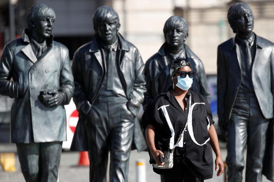 Una mujer camina delante de una estatua de los Beatles en Liverpool (Reuters)