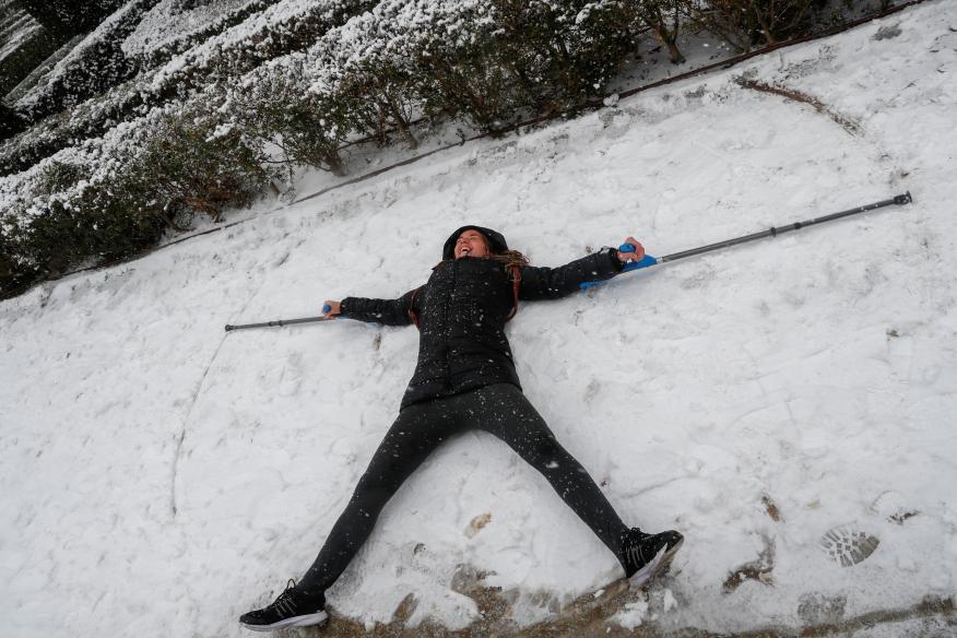 Mujer haciendo un ángel de nieve