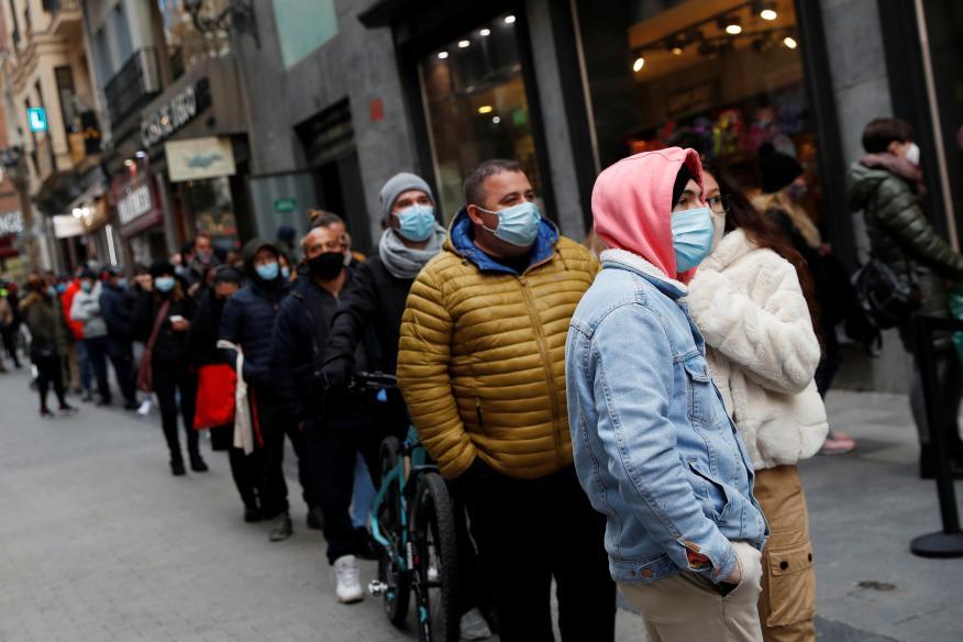 Personas haciendo fila esperando para comprar lotería en Doña Manolita, Madrid, España.