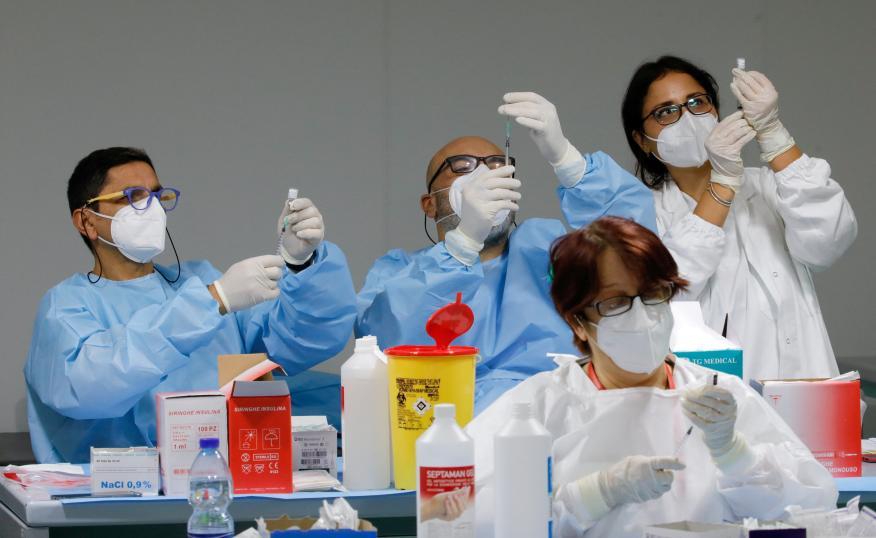 Varios médicos preparan dosis de la vacuna contra el COVID-19
