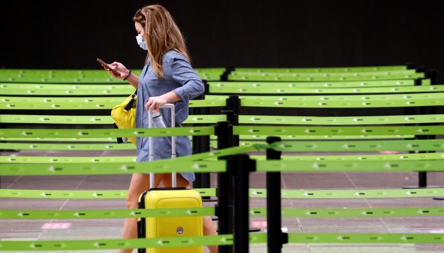 Una pasajera con mascarilla se dirige a los mostradores de facturación del aeropuerto de Barcelona-El Prat