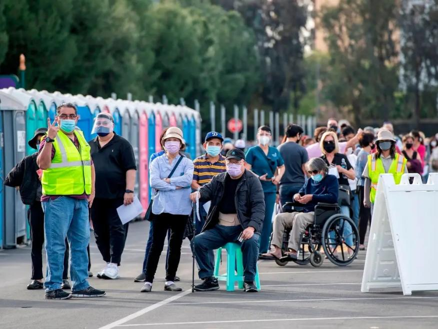 People wait in line in a Disneyland parking lot to receive Covid-19 vaccines on the opening day of the Disneyland Covid-19 vaccination site in Anaheim, California.