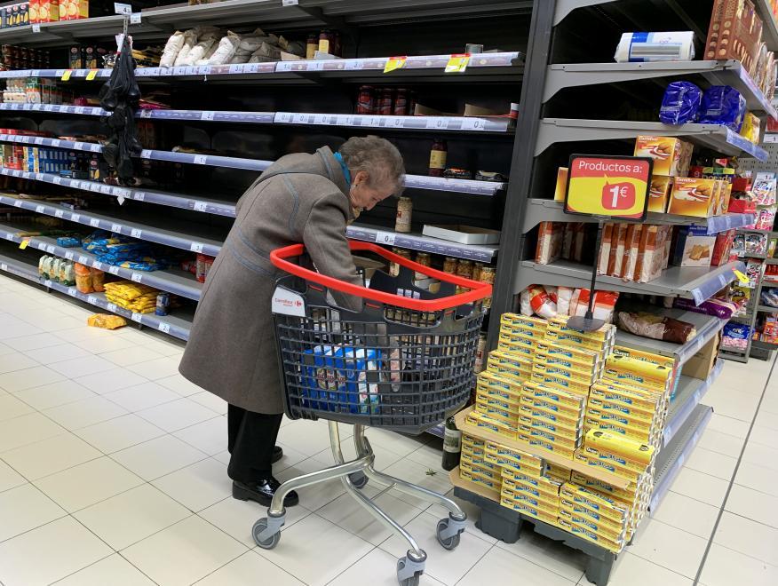 Una señora compra en un supermercado vacío en Madrid.